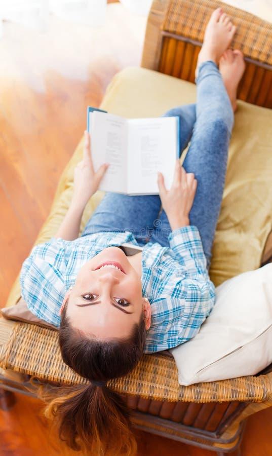 Kvinna som kopplar av med en hemmastadd bok och att le royaltyfria foton