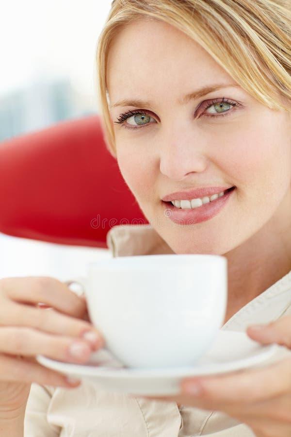 Kvinna som kopplar av med koppen av tea royaltyfri foto