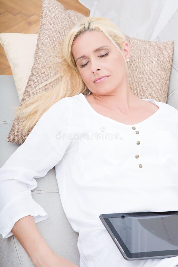Kvinna som kopplar av med minnestavlan på soffan arkivfoto
