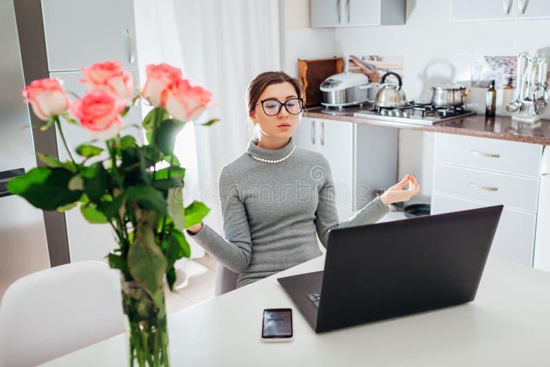 Kvinna som kopplar av, når att ha arbetat på bärbara datorn på modernt kök Ungt trött meditera för freelancer arkivfoto