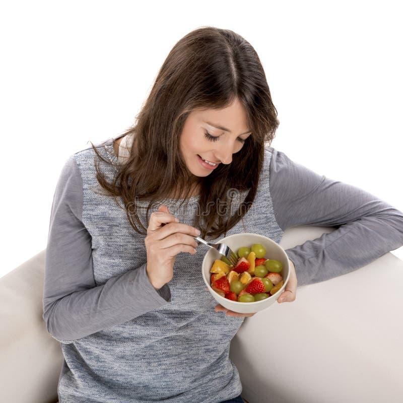 Kvinna som kopplar av och äter arkivbild