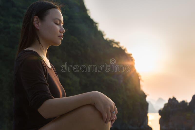 Kvinna som kopplar av och mediterar i natur, under solnedgång Fridsam zen arkivfoto