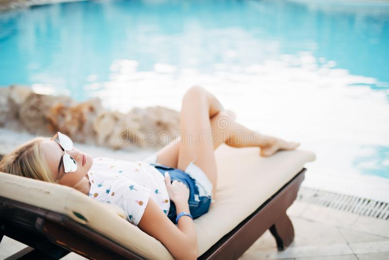 Kvinna som kopplar av på chaise-vardagsrum vid pölen på sommartid royaltyfria foton