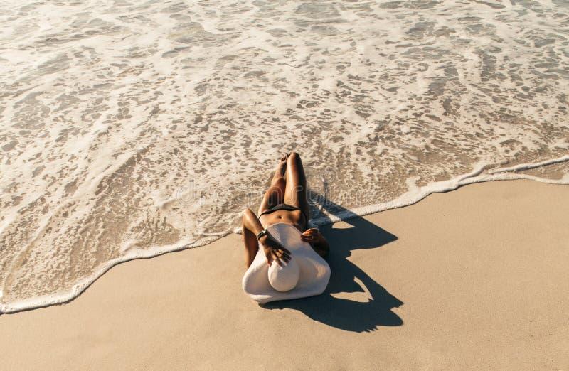 Kvinna som kopplar av på den bärande solhatten för strand royaltyfri bild