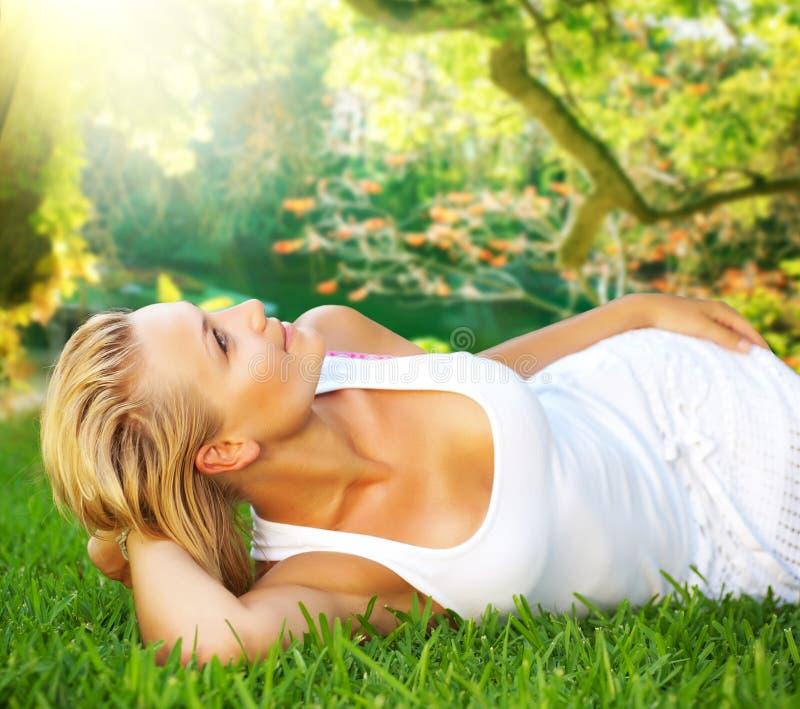 Kvinna som kopplar av på det gröna gräset royaltyfria foton