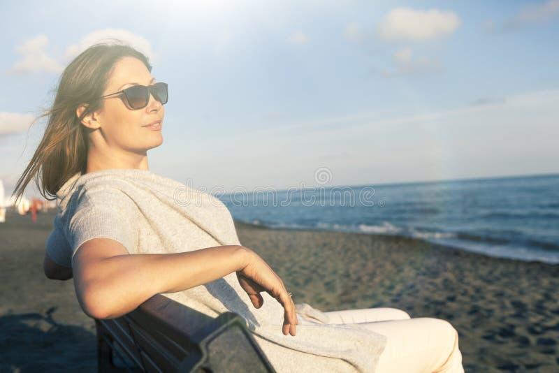 Kvinna som kopplar av på det iklädda fredsammanträdet för hav på bänken på stranden solglasögon arkivbilder