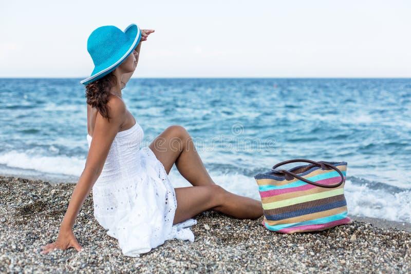 Kvinna som kopplar av på en sjösida arkivbild