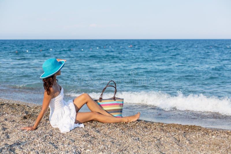 Kvinna som kopplar av på en sjösida royaltyfri foto