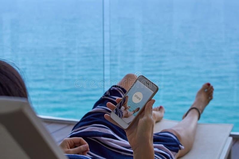 Kvinna som kopplar av på en solstol som delar ett foto arkivbild