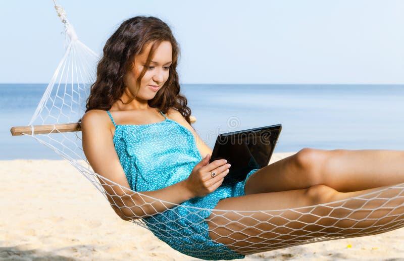 Kvinna som kopplar av på hängmattan och använder den digitala minnestavlan royaltyfri foto