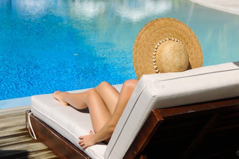 Kvinna som kopplar av på poolsiden arkivfoto