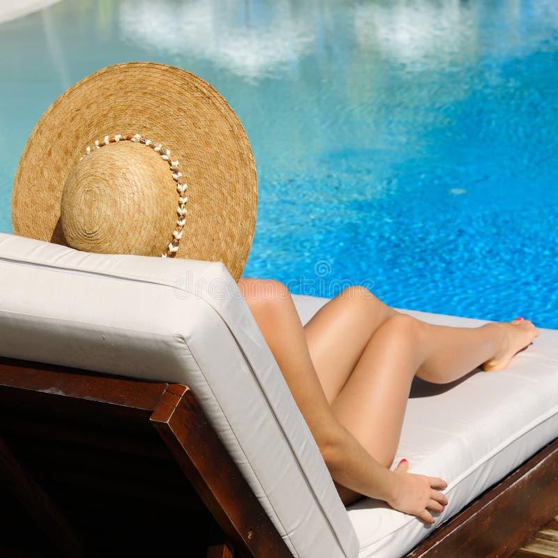 Kvinna som kopplar av på poolsiden royaltyfria foton