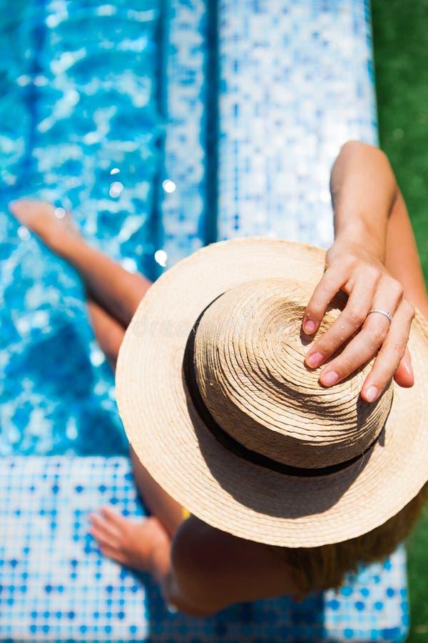 Kvinna som kopplar av på simbassängvattnet i varm solig dag Summ royaltyfri foto