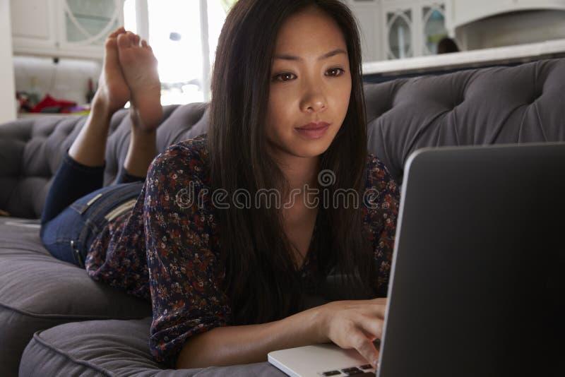 Kvinna som kopplar av på Sofa At Home Using Laptop royaltyfria foton