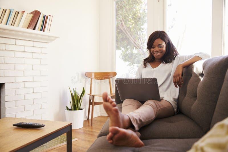 Kvinna som kopplar av på Sofa At Home Using Laptop royaltyfria bilder