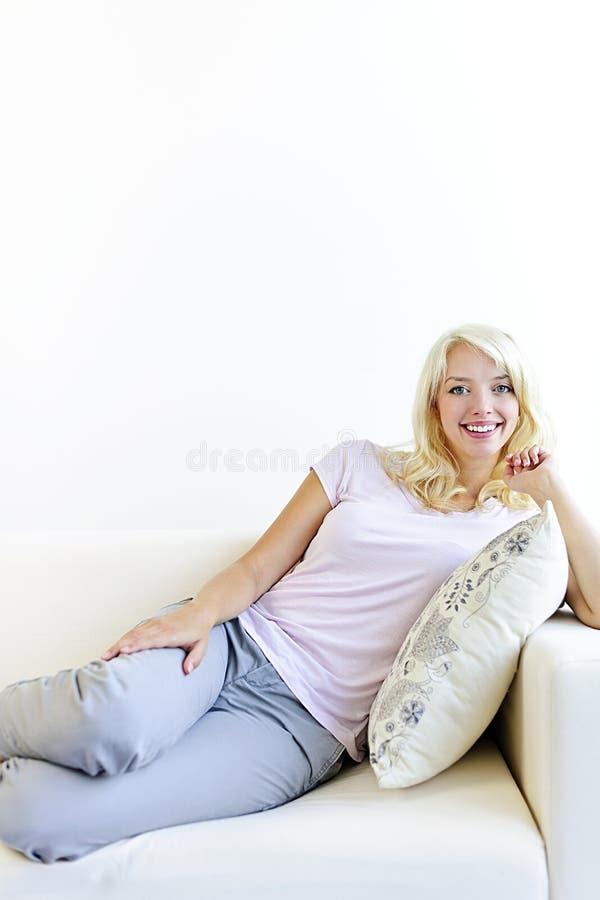 Kvinna som kopplar av på soffan royaltyfri foto