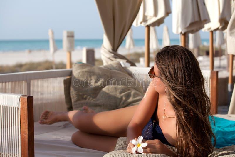 Kvinna som kopplar av på solstol royaltyfri foto