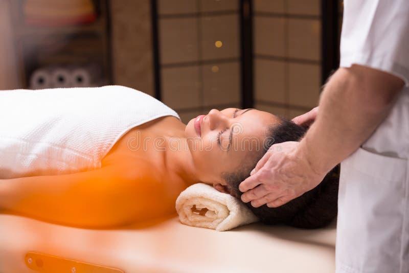 Kvinna som kopplar av under den head massagen arkivbild