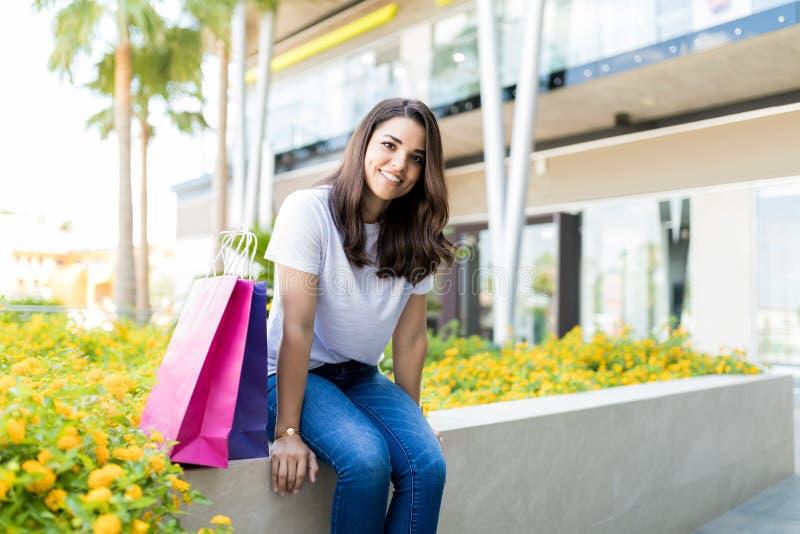 Kvinna som kopplar av vid pappers- påsar, når att ha shoppat utanför galleria arkivfoton
