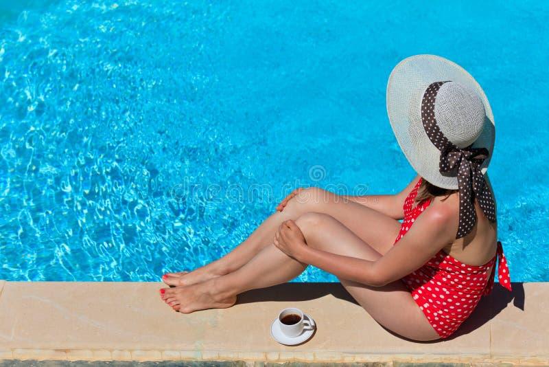 Kvinna som kopplas av av pölen med kaffe arkivbild
