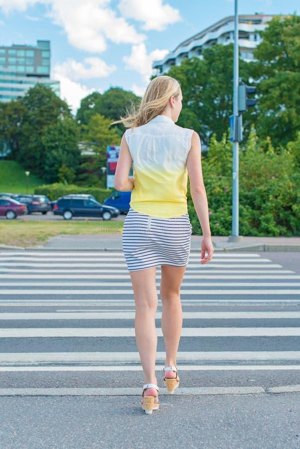 Kvinna som korsar vägen arkivbilder