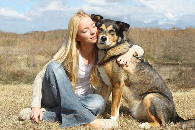 Kvinna som kramar den tyska herden Dog Outside royaltyfri bild