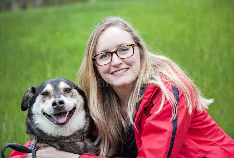 Kvinna som kramar hennes hund arkivbild