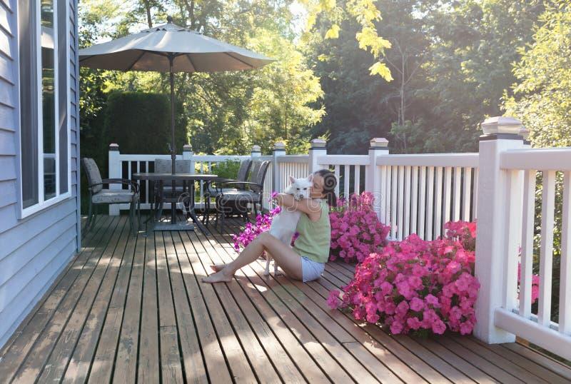 Kvinna som kramar hennes hund medan utomhus på hem- däck royaltyfria bilder
