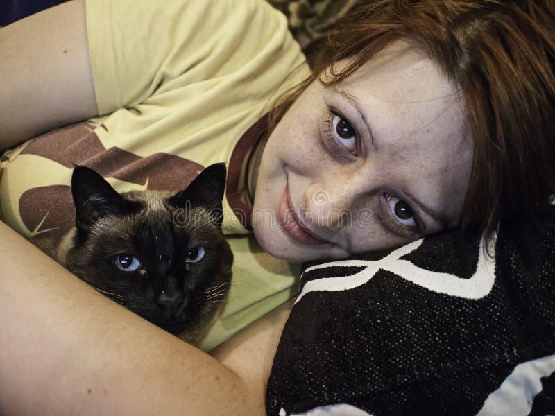 Kvinna som kramar katten royaltyfria foton