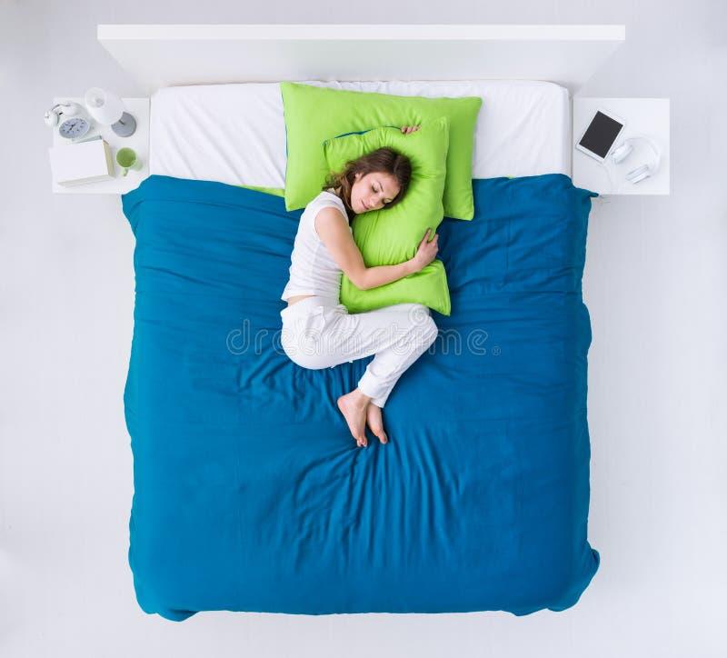 Kvinna som krullar upp i säng royaltyfria bilder