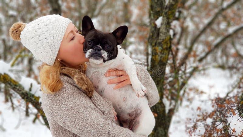 Kvinna som kysser en fransk bulldogg i snön fotografering för bildbyråer