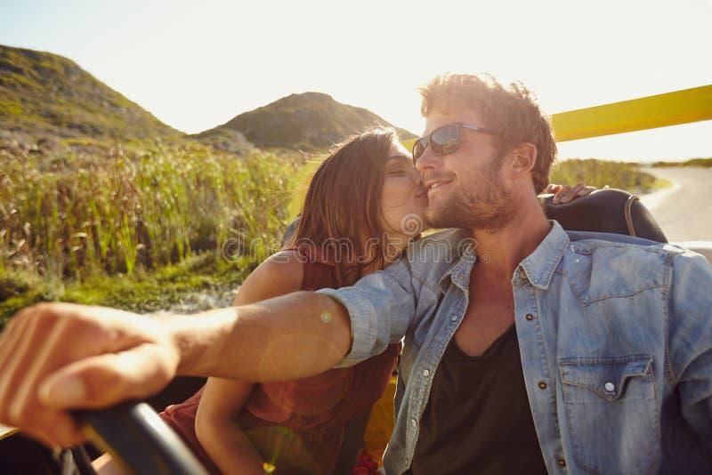 Kvinna som kysser hennes pojkvän som kör en bil arkivbild