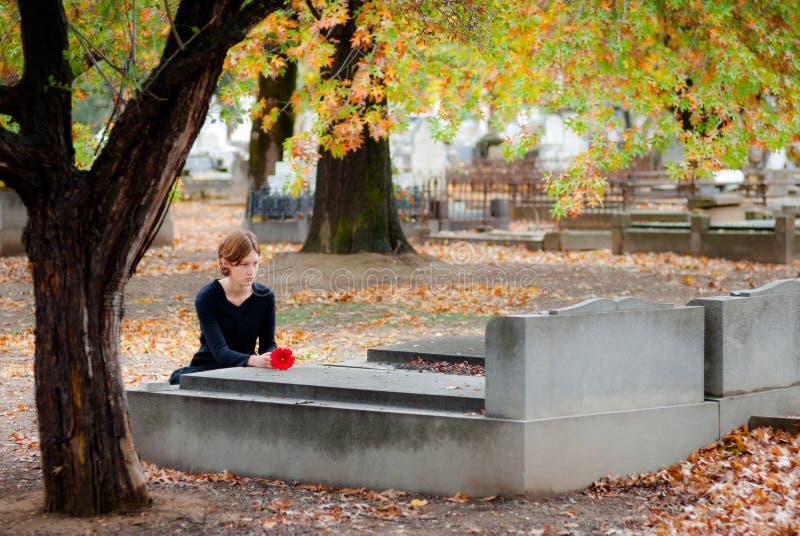 Kvinna som lägger blomman på grav i kyrkogård i Fal arkivbilder