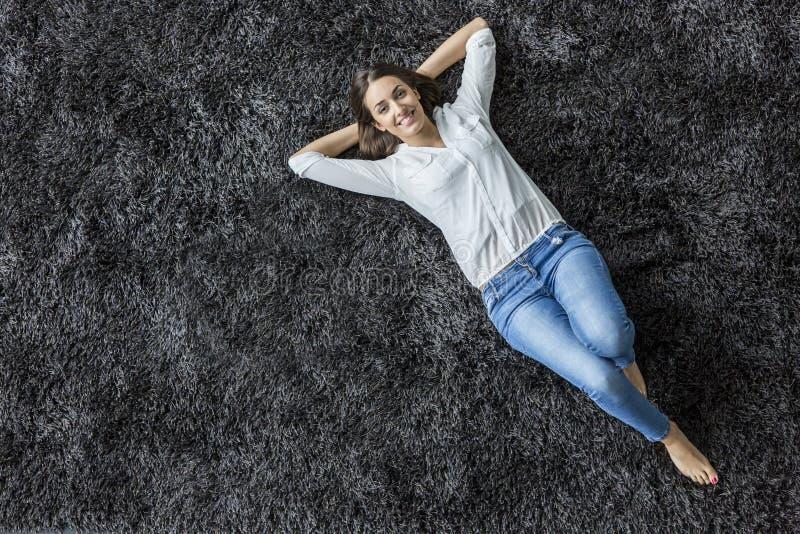 Kvinna som lägger på mattan fotografering för bildbyråer