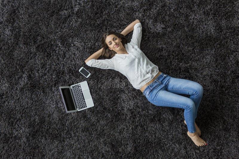 Kvinna som lägger på mattan royaltyfri fotografi