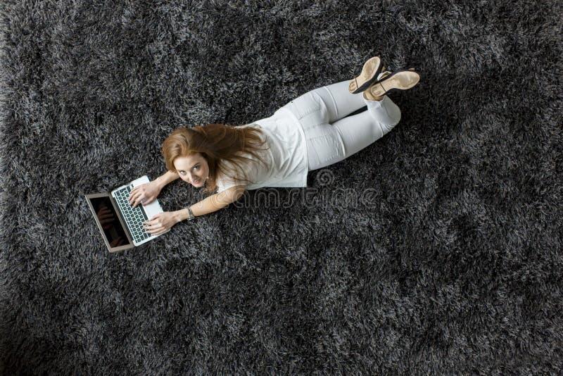 Kvinna som lägger på mattan arkivbild