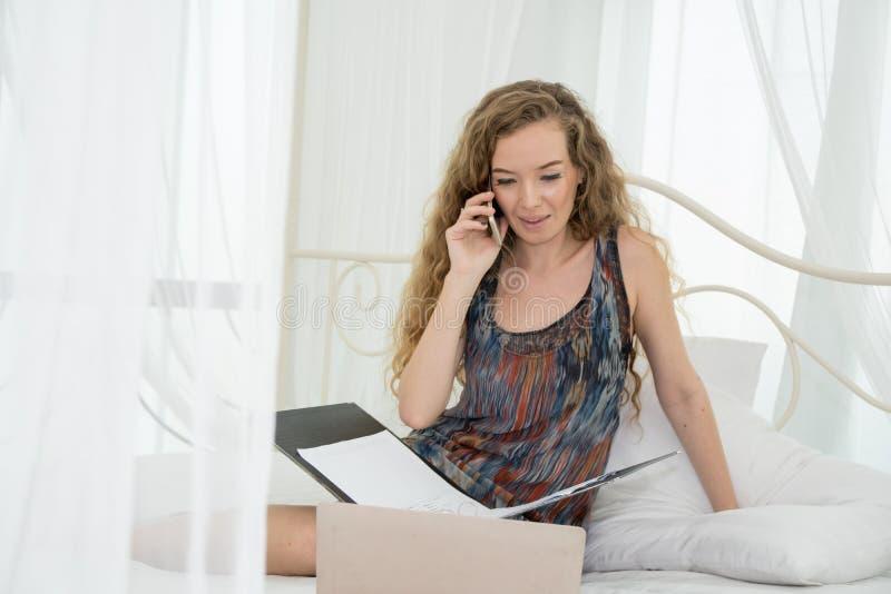 Kvinna som lägger på säng och använder bärbara datorn och telefonen royaltyfri foto