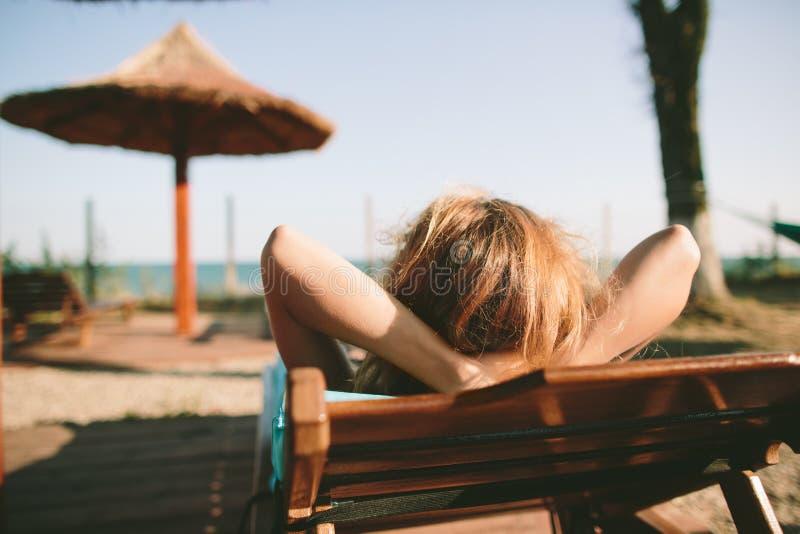 Kvinna som lägger på solsängen royaltyfri fotografi
