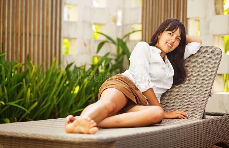 Kvinna som lägger på sunbed på semesterorten royaltyfri fotografi