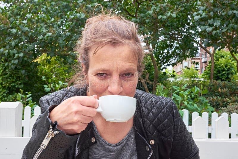 Kvinna som läppjar kaffe i en trädgård fotografering för bildbyråer