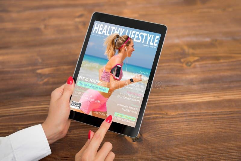 Kvinna som läser den sunda livsstiltidskriften på minnestavlan royaltyfri bild