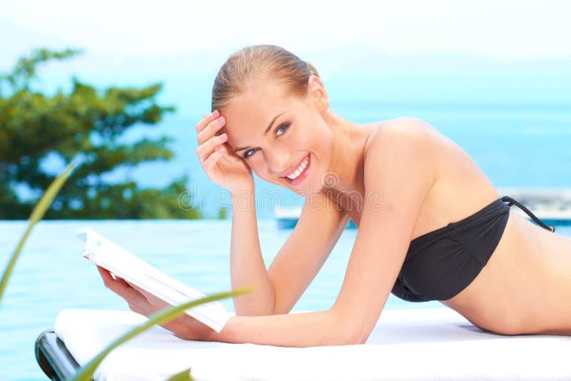 Kvinna som läser en bok bredvid simbassäng royaltyfria foton