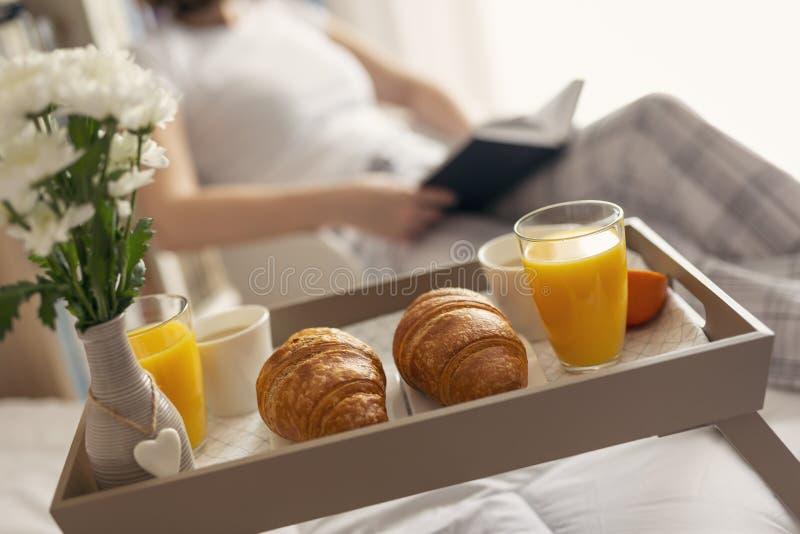 Kvinna som läser en bok för frukost royaltyfri foto