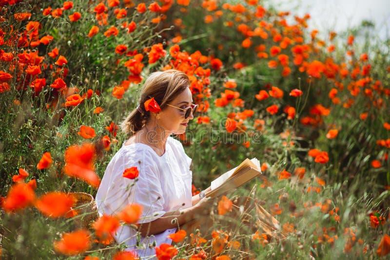 Kvinna som läser en bok i ett fält av röda vallmo i vårblommalynne royaltyfria bilder