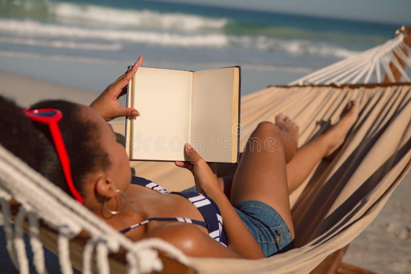 Kvinna som läser en bok, medan koppla av på hängmattan på stranden royaltyfri fotografi