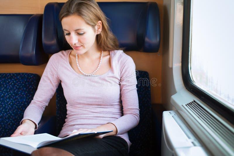 Kvinna som läser en bok medan på ett drev royaltyfri foto