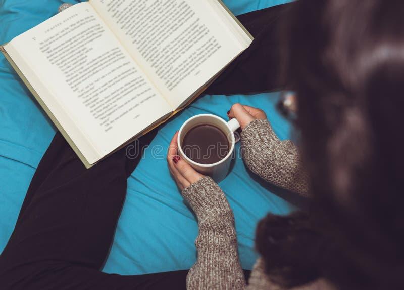 Kvinna som läser en bok och dricker kaffe i säng royaltyfria bilder