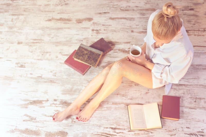 Kvinna som läser en bok och dricker te i hennes bekväma hem arkivfoton