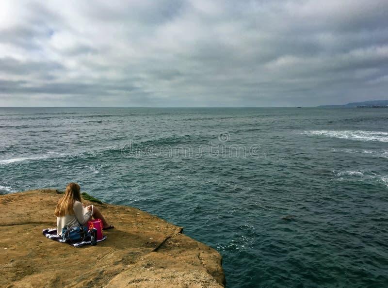 Kvinna som läser en bok på en sjösidaklippa som ut ser på Stilla havet arkivfoton