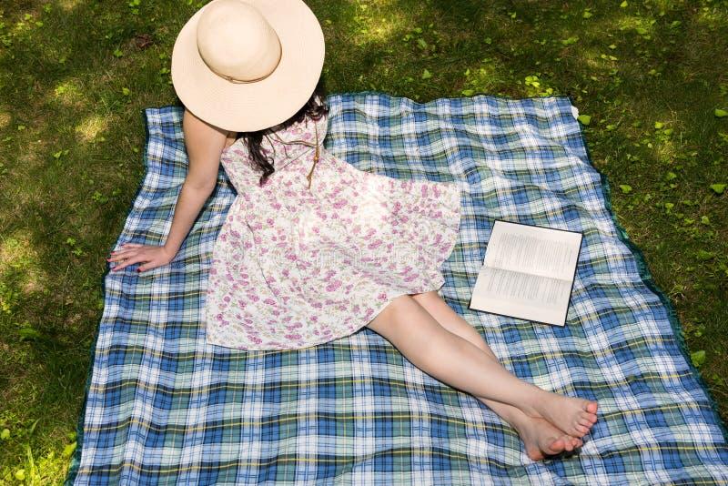 Kvinna som läser en bok utanför i gräset royaltyfria foton